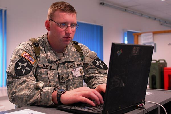 Voter in military fatigues votes on computer