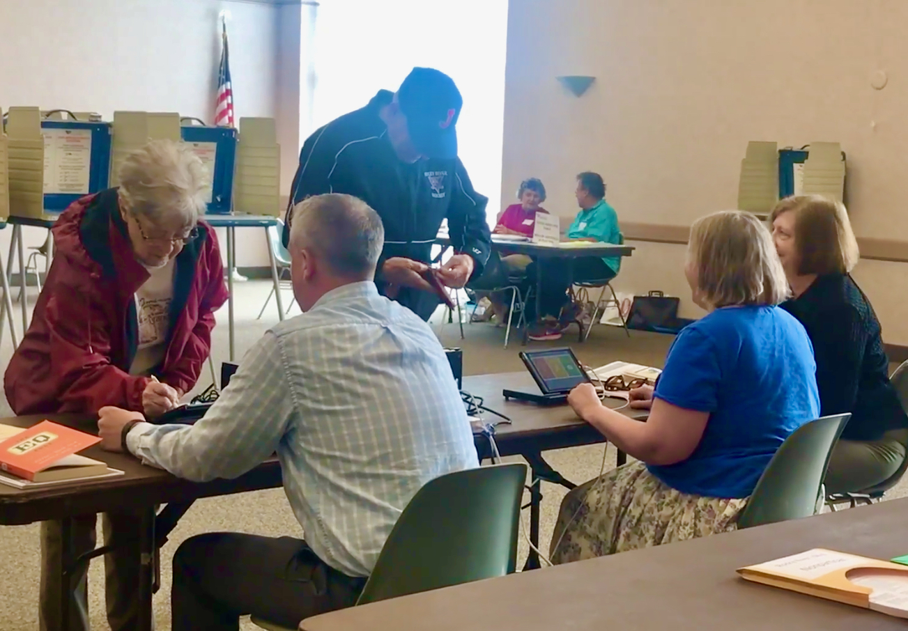 Poll workers check in voters on Precinct Central electronic poll books